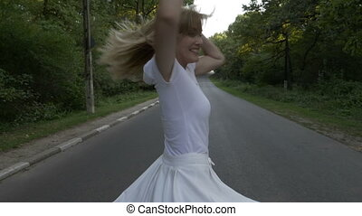 Attractive young lady enjoying a summer day in nature running in the forest