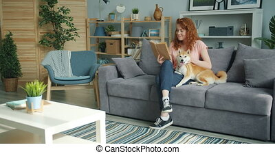 Attractive young lady enjoying interesting book and stroking cute dog at home sitting on couch smiling. Modern youth, lifestyle and interior concept.