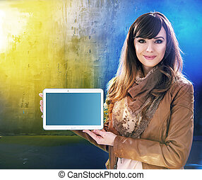 Attractive young lady holding a tablet