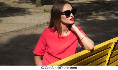 attractive young lady in red suit and sunglasses sits on a bench at the park