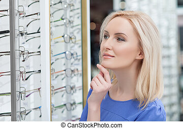Attractive young lady is buying new spectacles