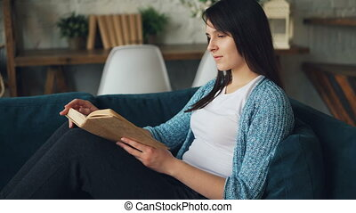 Attractive young lady is reading book and smiling sitting on...