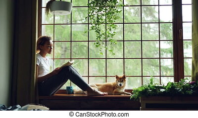 Attractive young lady is reading book sitting on windowsill...
