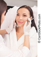 Attractive young lady is visiting her cosmetician