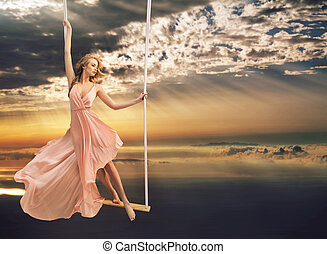 Attractive young lady on a swing above the sea