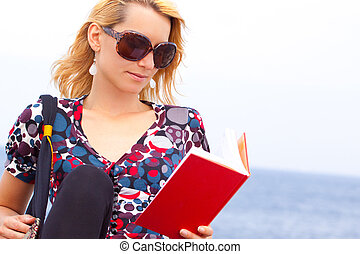 Attractive young lady reading a book.