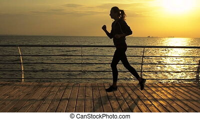 Attractive young lady with blond color of hair, running near the sea.