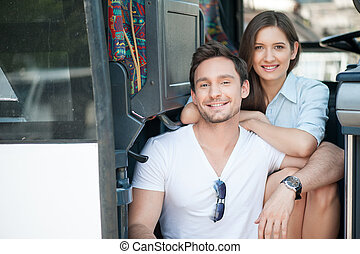 Attractive young loving couple is using public transport