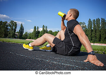 Attractive young male runner is very thirsty