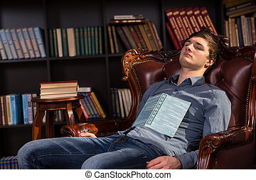 Attractive young man asleep in a library