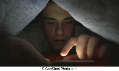 Attractive young man browsing social media on a smart phone in bed