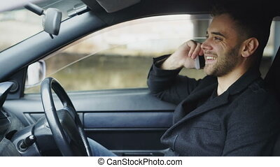 Attractive young man chatting smart phone while sitting inside his car outdoors
