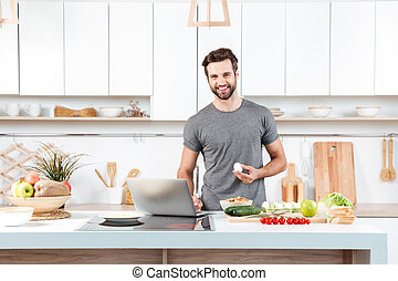 Attractive young man cooking with mixing bowl and looking at...