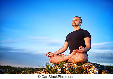 Attractive young man doing yoga on the rock against blue sky with clouds.
