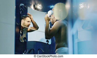 Attractive young man dries hair in the mirror