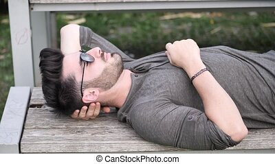 Attractive young man in city park in a summer day