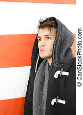 Attractive young man in hoodie against white and orange wall