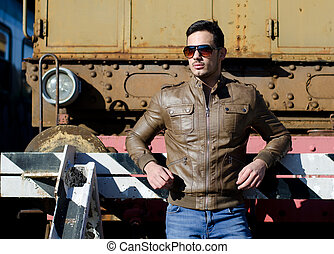 Attractive young man in leather jacket and jeans in front of old train