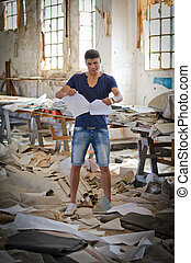 Attractive young man in messy office or working place