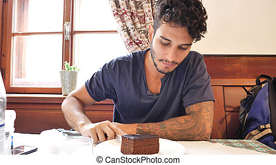 Attractive young man in restaurant eating