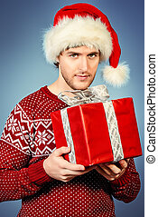 Attractive young man in Santa Claus cap holding a gift box and smiling.