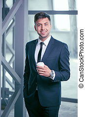 Attractive young man in suit is enjoying hot drink