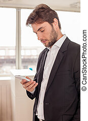 Attractive young man in suit is using telephone