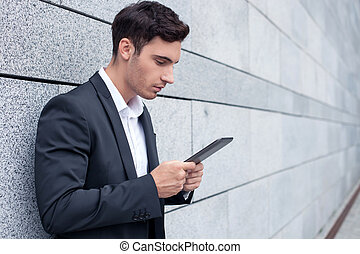 Attractive young man in suit is working with laptop