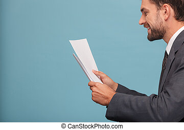 Attractive young man in suit with documents