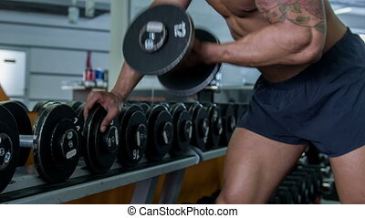 Handsome athlete is raising dumbbell in his left hand. He is leaning with his right hand on the rack with dumbbells. He is strained and serious