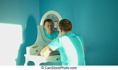Attractive young man is thoughtful and looks at himself in the mirror