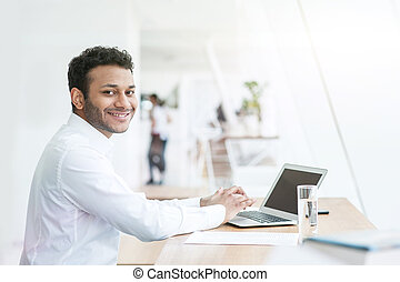 Attractive young man is working on a computer