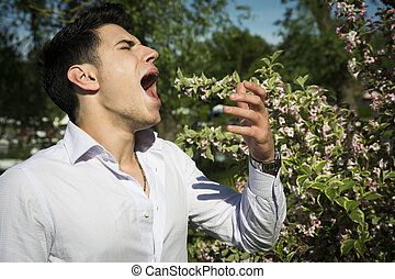 Attractive young man next to flowers sneezing because of hay-fever allergy