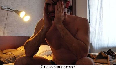 Attractive young man on bed with headache