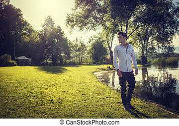 Attractive young man on lake in sunny day