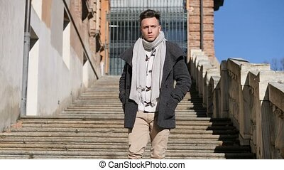 Attractive young man outdoor walking down stone stairs