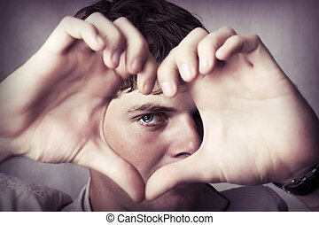 Attractive young man show love sign