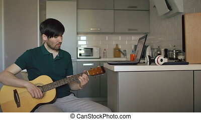 Attractive young man sitting at kitchen learning to play guitar using laptop computer at home