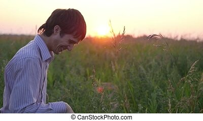 attractive young man smiling and looking in the filed at sunset