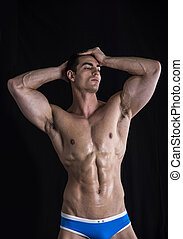 Attractive young man standing with muscular ripped body