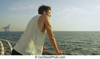 Attractive young man staying on wooden boardwalk after morning jogging.