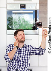 Attractive young man with a glass of wine in a modern kitchen.