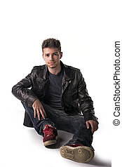 Attractive young man with leather jacket sitting on the floor sm