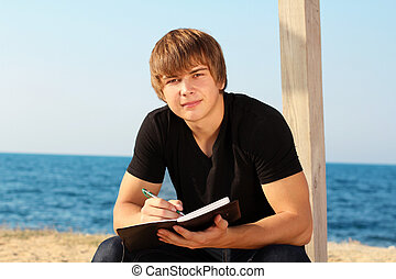 Attractive young man with writing pad on the beach