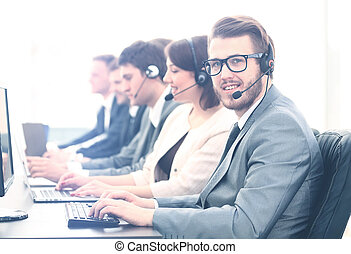 Attractive young man working in a call center with his...