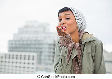 Attractive young model in winter clothes blowing a kiss to the camera outside on a cloudy day