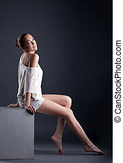 Attractive young model posing sitting on cube