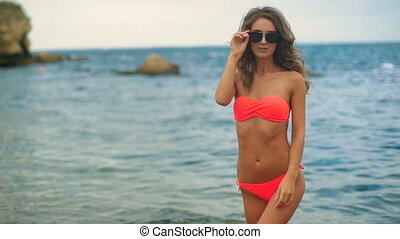 Attractive young model wearing swimming suit and sunglasses posing on camera in a beach.