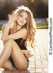 Attractive young model with long blonde hair posing in rays of sun