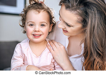Attractive young mother hugging her beloved child